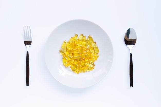 Capsules d'huile de poisson sur plat blanc, folk et cuillère Photo Premium