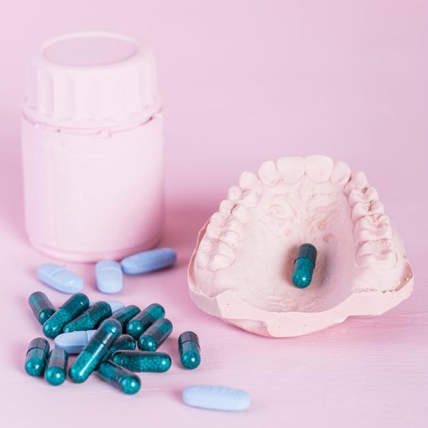 Capsules et pilules avec bouteille et prothèse sur le fond rose Photo gratuit