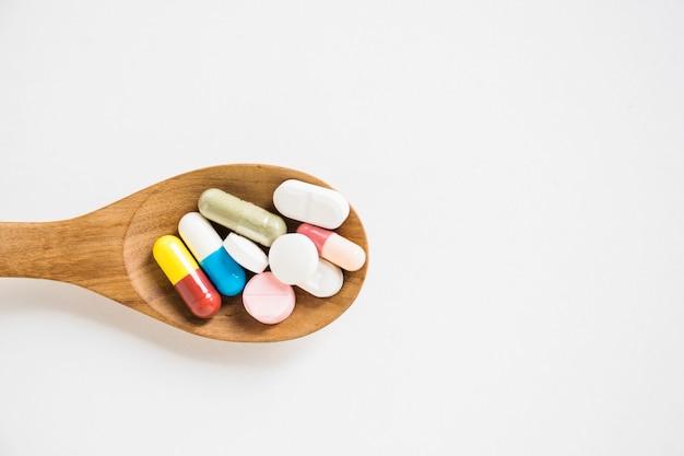 Capsules et pilules sur une cuillère en bois sur fond blanc Photo gratuit