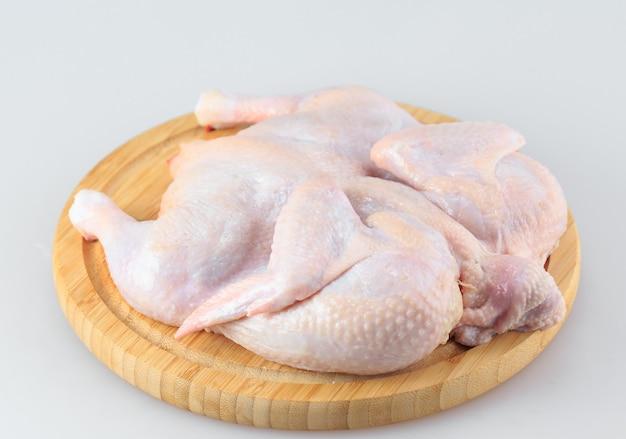 Carcasse de poulet cru sur la planche à découper isolée on white Photo Premium
