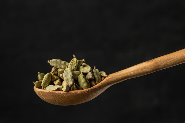 Cardamome assaisonnement dans une cuillère en bois se bouchent Photo Premium