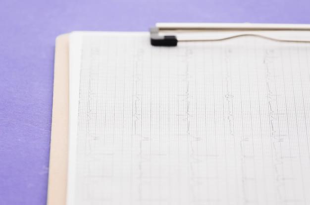 Cardiogramme; graphique ecg dans le presse-papiers sur fond violet Photo gratuit