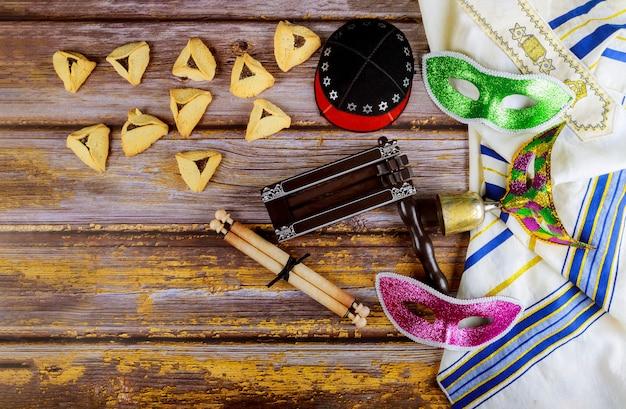 Carnaval Juif Célébration De Pourim Sur Les Biscuits Hamantaschen, Bruiteur Et Masque Avec Parchemin Photo Premium
