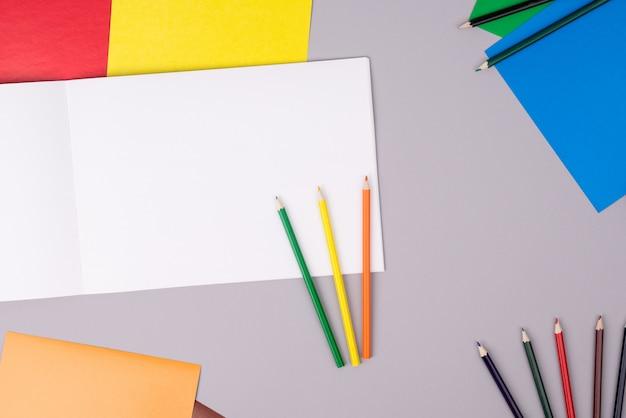 Carnet de croquis avec des crayons de couleur et du papier de couleur sur gris Photo Premium