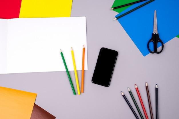 Carnet de croquis avec des crayons de couleur, un téléphone portable et du papier de couleur sur gris Photo Premium