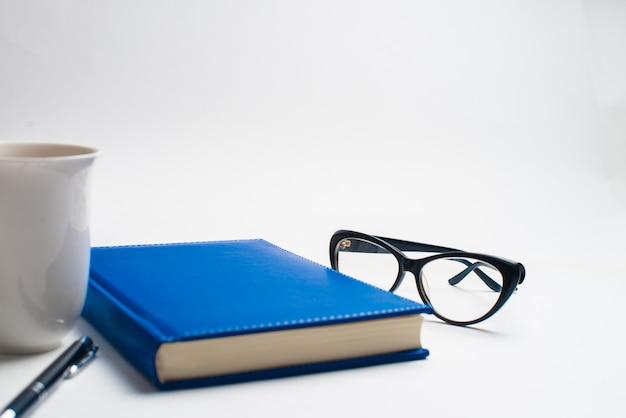 Carnet avec des lunettes et un stylo, livre avec des lunettes, carnet bleu avec des lunettes, livre avec une tasse de thé Photo Premium