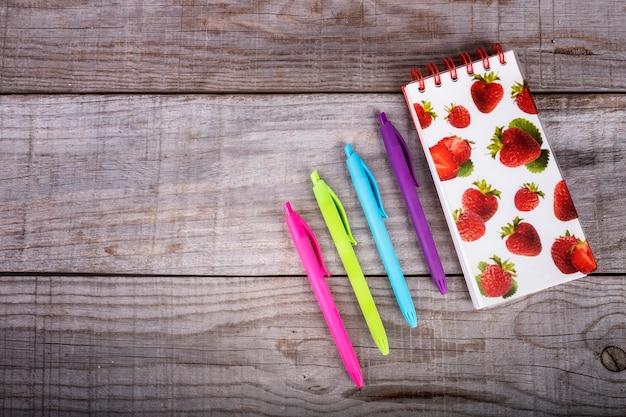 Carnet de notes aux fraises et ensemble de stylos de couleurs sur fond en bois Photo Premium