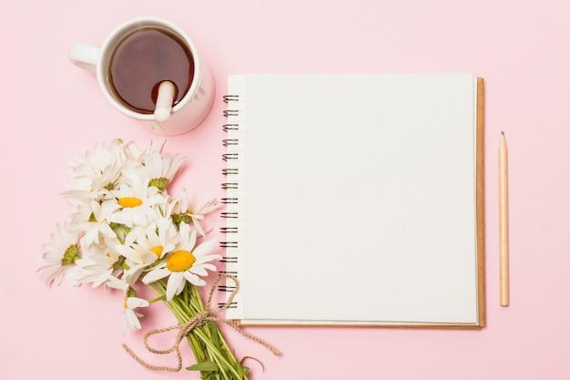 Carnet de notes près de fleurs et tasse de boisson Photo gratuit