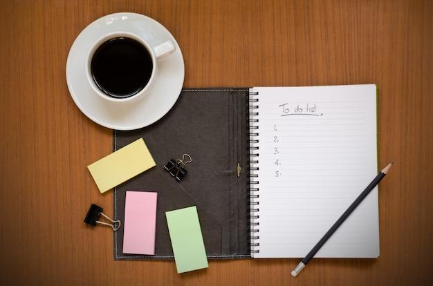 Carnet de notes recyclé avec une liste de tâches en main dans la note papier Photo Premium