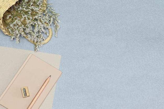 Le carnet de notes rose, crayon en bois et taille-crayon, panier de fleurs sur le bureau bleu Photo Premium