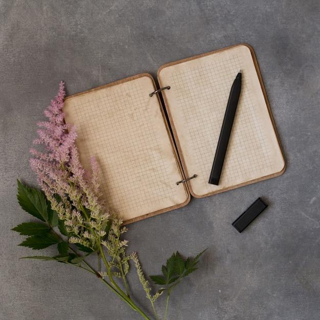 Carnet de notes vides avec des fleurs roses, astilba multicolore, maquette sur un fond gris. espace de texte. ancien. concept de message ou d'invitation de mariage ou d'anniversaire Photo Premium