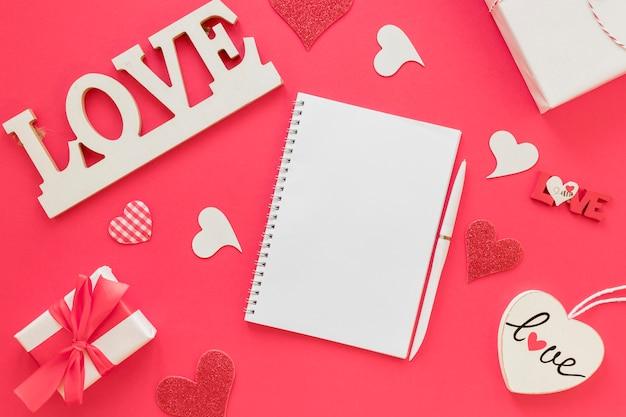 Carnet saint-valentin avec stylo et cadeaux Photo gratuit