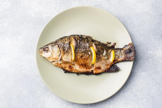 Carpe de poisson au four avec citron vert sur une assiette. Photo Premium