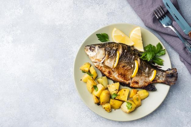 Carpe de poisson au four avec citron vert et pommes de terre sur une assiette. espace de copie Photo Premium