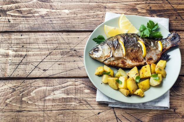 Carpe de poisson au four avec citron vert et pommes de terre sur une assiette. fond en bois espace de copie Photo Premium