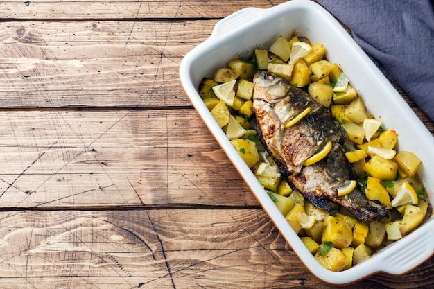 Carpe de poisson au four avec pommes de terre dans une poêle en céramique. style rustique. espace de copie Photo Premium