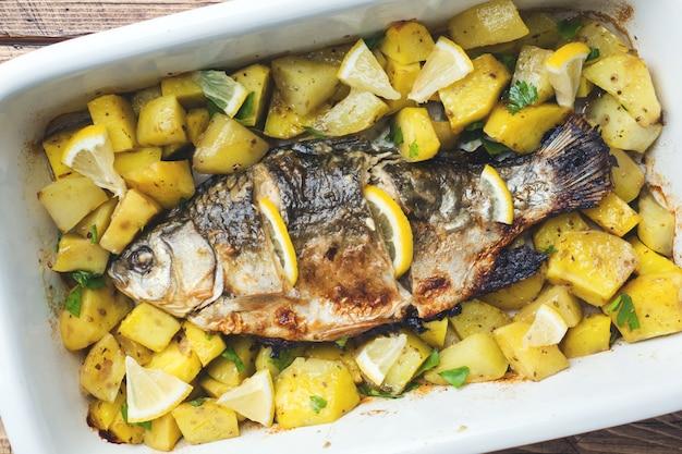 Carpe de poisson au four avec pommes de terre dans une poêle en céramique. style rustique. Photo Premium