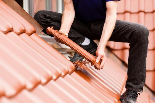 Carreleur couvrant le toit avec une nouvelle tuile Photo Premium