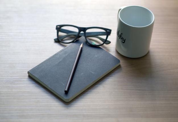 Carrière de l'écrivain sur le bureau avec un livre de tasse à café blanc, crayon et lunettes Photo Premium