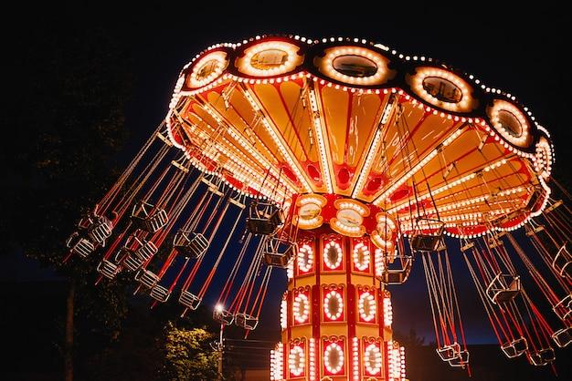 Carrousel à chaîne pivotante lumineux dans un parc d'attractions dans la nuit Photo Premium