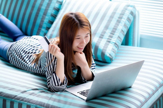 Carte de crédit de belle femme asiatique couchée avec ordinateur portable Photo Premium