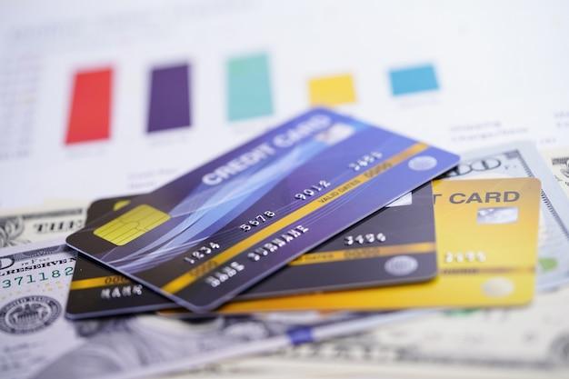 Carte de crédit avec des billets en dollars américains sur du papier millimétré. Photo Premium