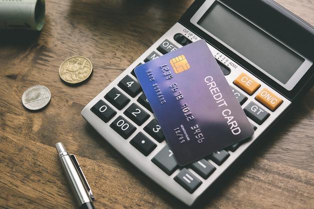 Carte de crédit avec calculatrice et de l'argent sur la table Photo Premium