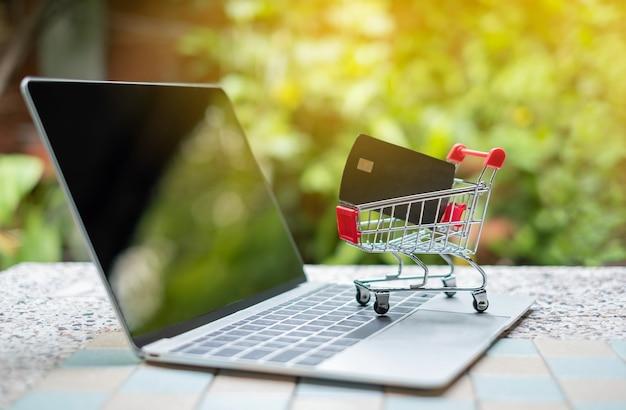 Carte de crédit dans un petit panier sur un ordinateur portable. concepts achats en ligne Photo Premium