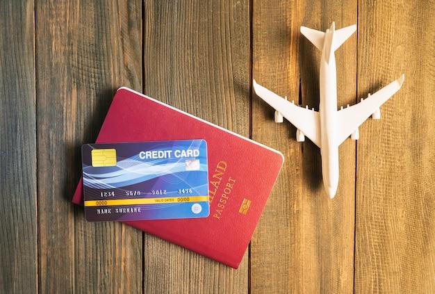Carte De Crédit Mise Sur Le Passeport Et Le Modèle D'avion Sur Table En Bois, Préparation Au Concept De Voyage Photo Premium