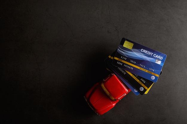 La carte de crédit sur le modèle de ramassage rouge sur le sol noir Photo gratuit