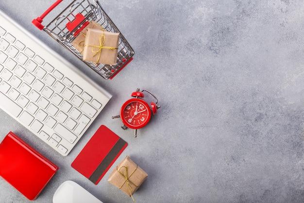 Carte de crédit rouge, clavier et cadeaux de noël sur une table grise à plat, espace de copie. Photo Premium