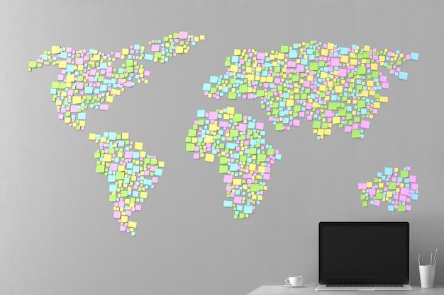 Carte du monde d'après les autocollants collés au mur avec un ordinateur portable debout Photo Premium
