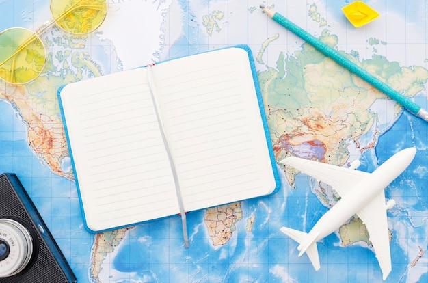 Carte du monde avec carnet de voyage Photo gratuit