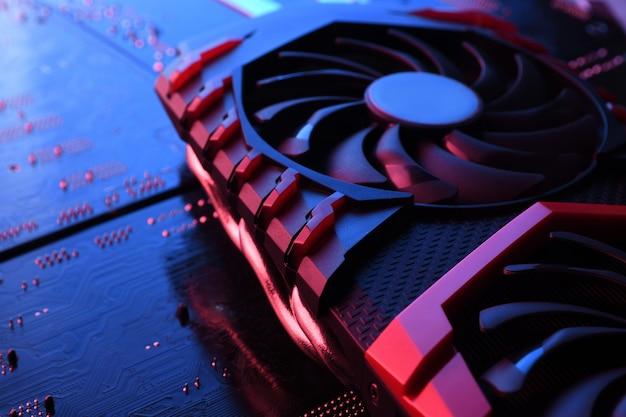 Carte Graphique De Jeu D'ordinateur, Carte Vidéo Avec Deux Refroidisseurs Sur Circuit Imprimé, Fond De Carte Mère. Fermer. Avec Un éclairage Rouge-bleu. Photo Premium