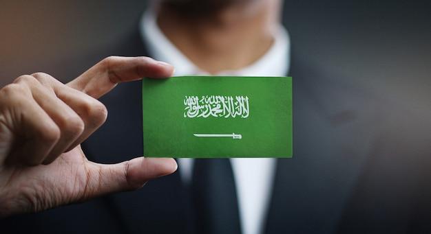 Carte de holding homme d'affaires du drapeau de l'arabie saoudite Photo Premium