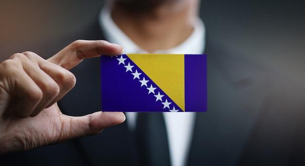 Carte de holding homme d'affaires du drapeau de la bosnie-herzégovine Photo Premium