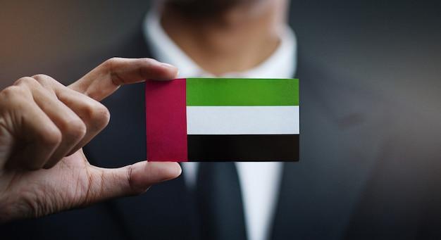 Carte de holding homme d'affaires du drapeau des émirats arabes unis Photo Premium