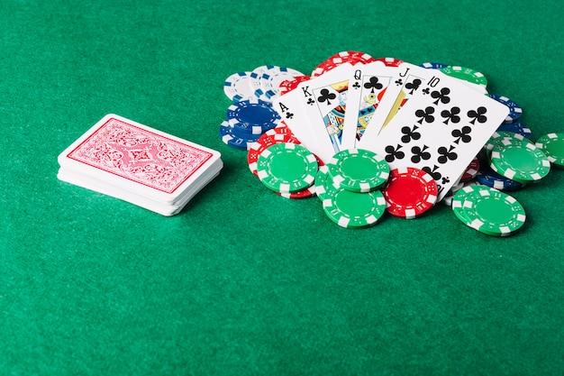 Carte à jouer et jetons de casino sur une table de poker verte Photo gratuit