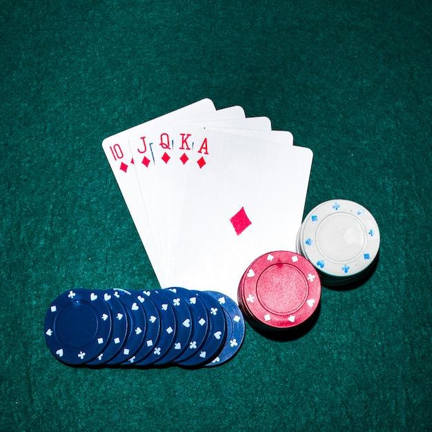 Carte à jouer à la quinte royale et jetons de casino sur la table de poker Photo gratuit