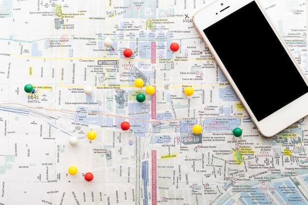 Carte marquée avec des épingles et un téléphone Photo gratuit