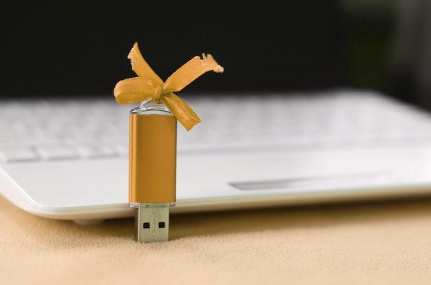 Carte mémoire flash usb orange avec un arc se trouve sur la couverture Photo Premium