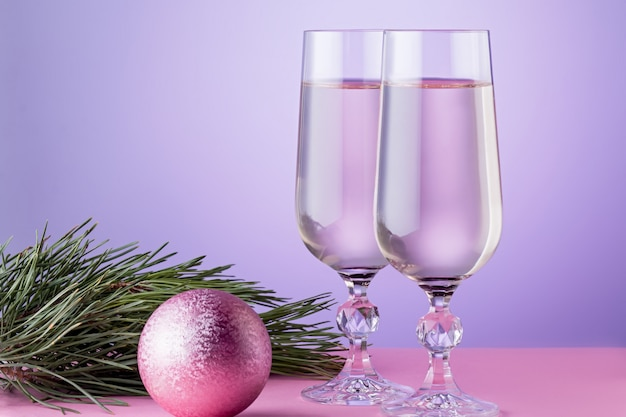 Carte De Noël Avec Deux Verres De Champagne, Décorations De Noël, Branche De Sapin Aux Couleurs Roses. Espace Copie Photo Premium