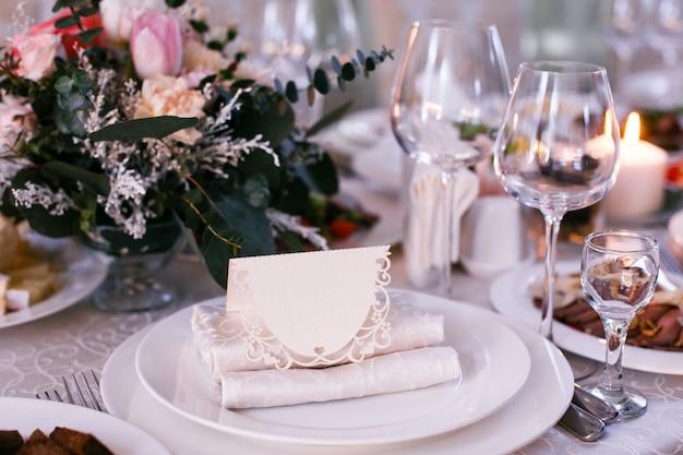Carte avec le nom de l'invité se trouve sur une assiette Photo Premium