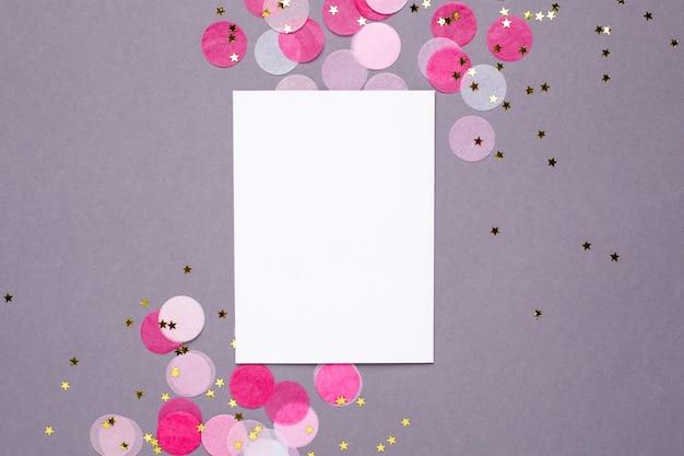 Carte présente et confettis roses avec des étoiles dorées sur fond gris Photo Premium