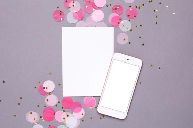 Carte présente, maquette de téléphone portable et confettis roses avec des étoiles dorées sur fond gris Photo Premium