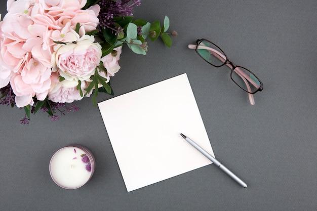 Carte et stylo avec bouquet de roses sur gris Photo Premium