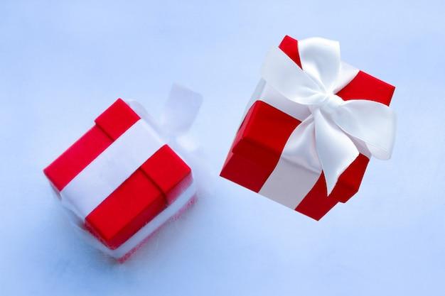 Carte de vacances d'hiver ou affiche de vente avec coffret figé dans une boîte cadeau glacée et rouge avec ruban de satin blanc festif avec archet Photo Premium