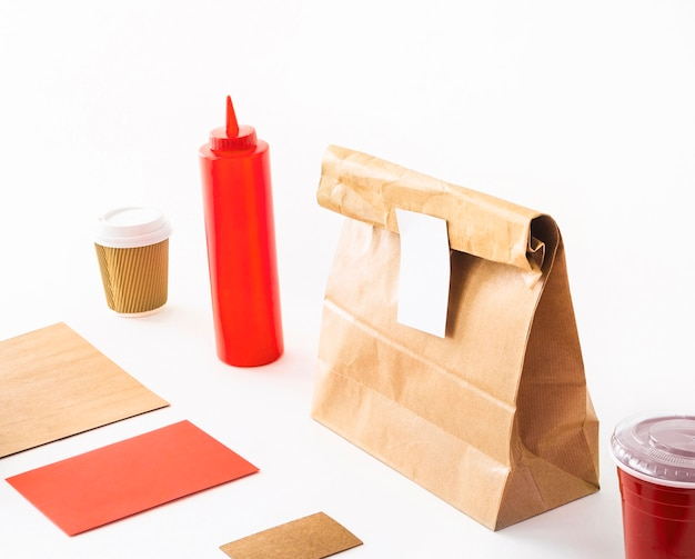 Carte vierge avec une tasse de café; bouteille de sauce; et paquet sur fond blanc Photo gratuit