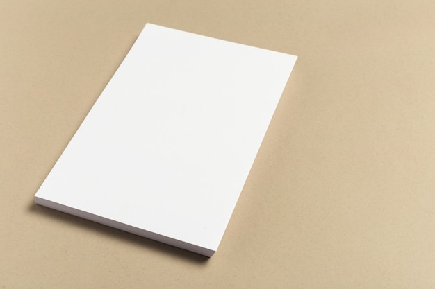 Carte de visite blanche sur une table en bois. portrait vierge a4. Photo Premium