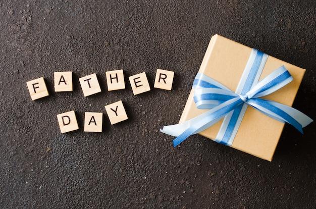 Carte de voeux bonne fête des pères avec une boîte cadeau décorée sur fond sombre. Photo Premium